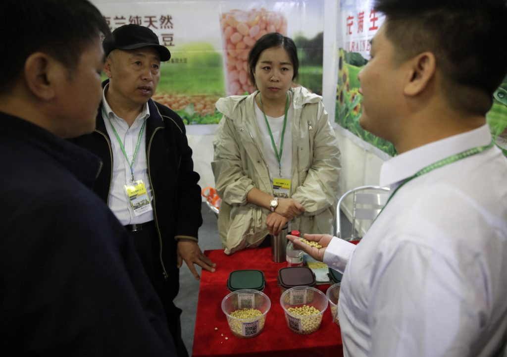 A Chinese exhibitor explains to visitors about his company's raw soybeans at an international trade exhibition Thursday in Shanghai. China's global trade balance swung to a rare deficit in March as exports contracted 2.7% from a year earlier.