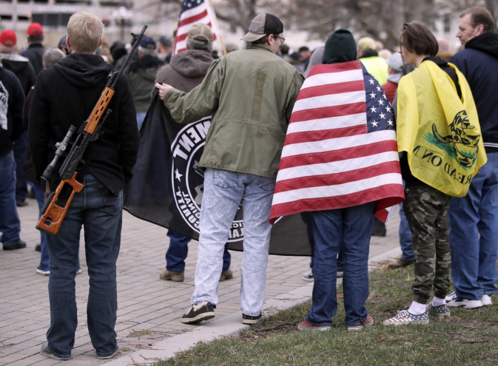 Pro-gun supporters wrapped in flags and carrying guns rally at the Kansas Statehouse in Topeka on Saturday. The rallies come less than three weeks after hundreds of thousands marched in Washington, New York and elsewhere to demand tougher gun laws after the February school shooting in Parkland, Fla.