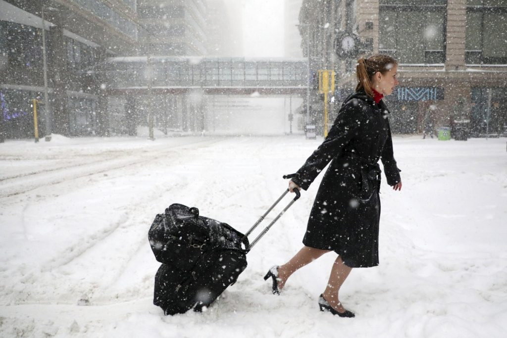 Delta Airlines flight attendant Victoria Flees trudges through the snow with her bags in downtown Minneapolis after her flight to Paris was grounded because of weather.