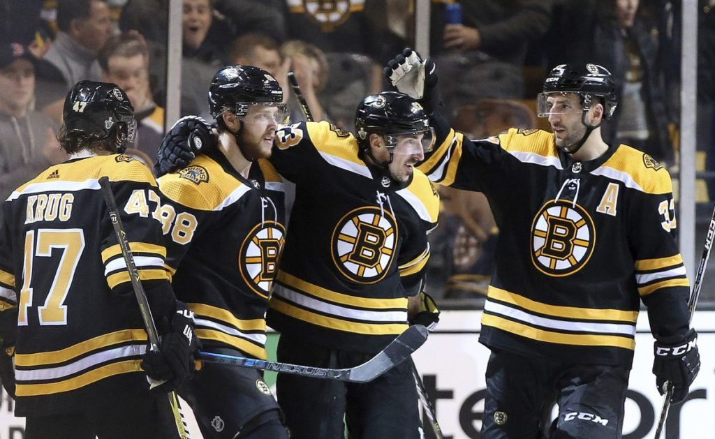 David Pastrnak, second from left, is congratulated by Torey Krug, left, Brad Marchand, center, and Patrice Bergeron after he scored his third goal of the game Saturday in Boston's 7-3 win over the Maple Leafs.