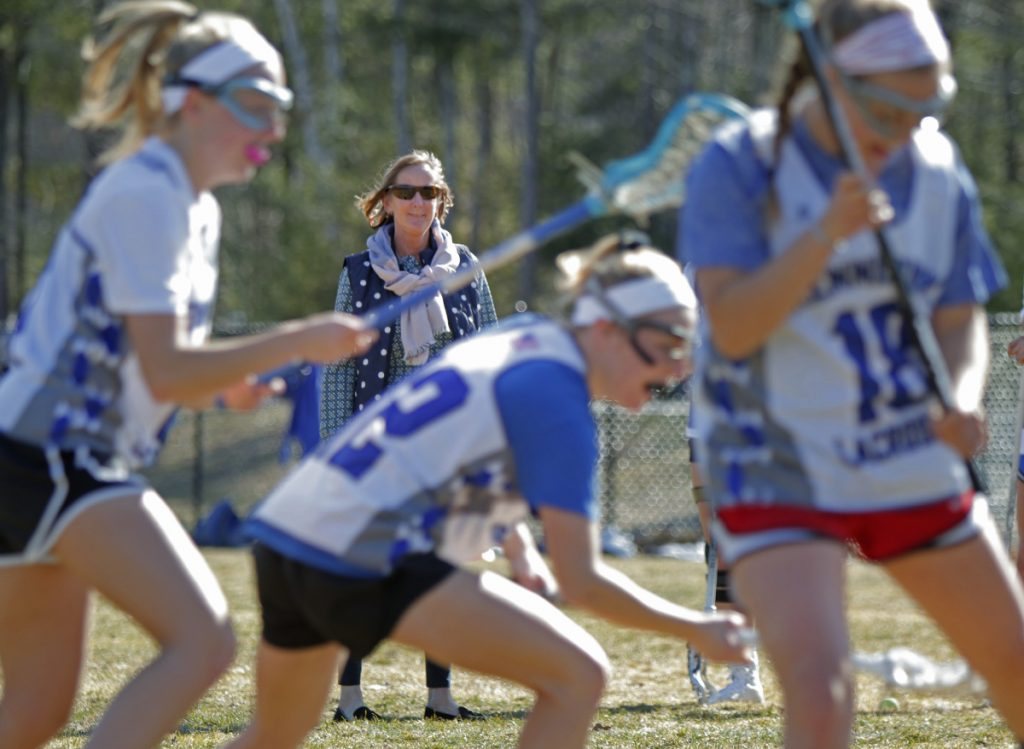 Kennebunk girls' lacrosse coach Annie Barker watches her players run through a drill. Kennebunk, winners of the past two Class B championships, moves up to Class A this season as the sport adds a third enrollment class. (Staff photo by Gregory Rec/Staff Photographer)