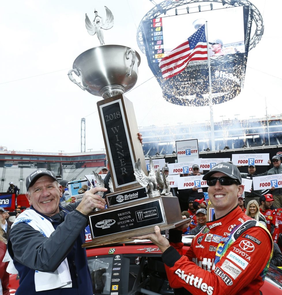 Food City President and CEO Steve Smith, left, holds the trophy with race winner Kyle Busch after the NASCAR Cup Series race on Monday in Bristol, Tenn.