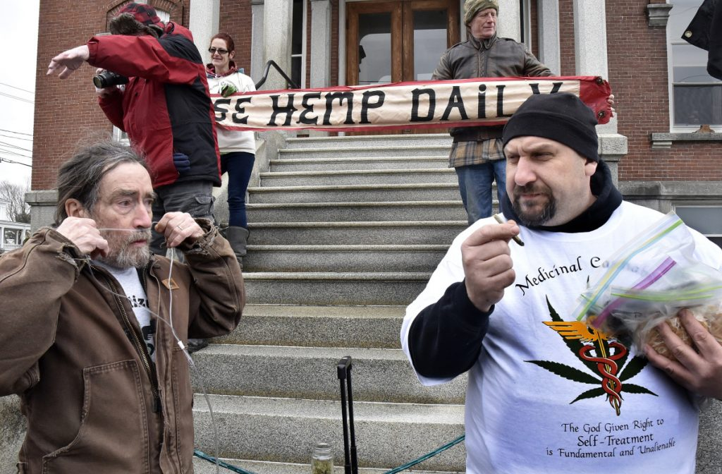 Marijuana advocate Donny Christen, left, who suffers chronic obstructive pulmonary disease, inserts oxygen tubes to help him breathe, as medicinal caregiver Dennis Hammac smokes a joint and distributes edible pot products at the annual Patriot's Day smoke-in at the Somerset County Courthouse.