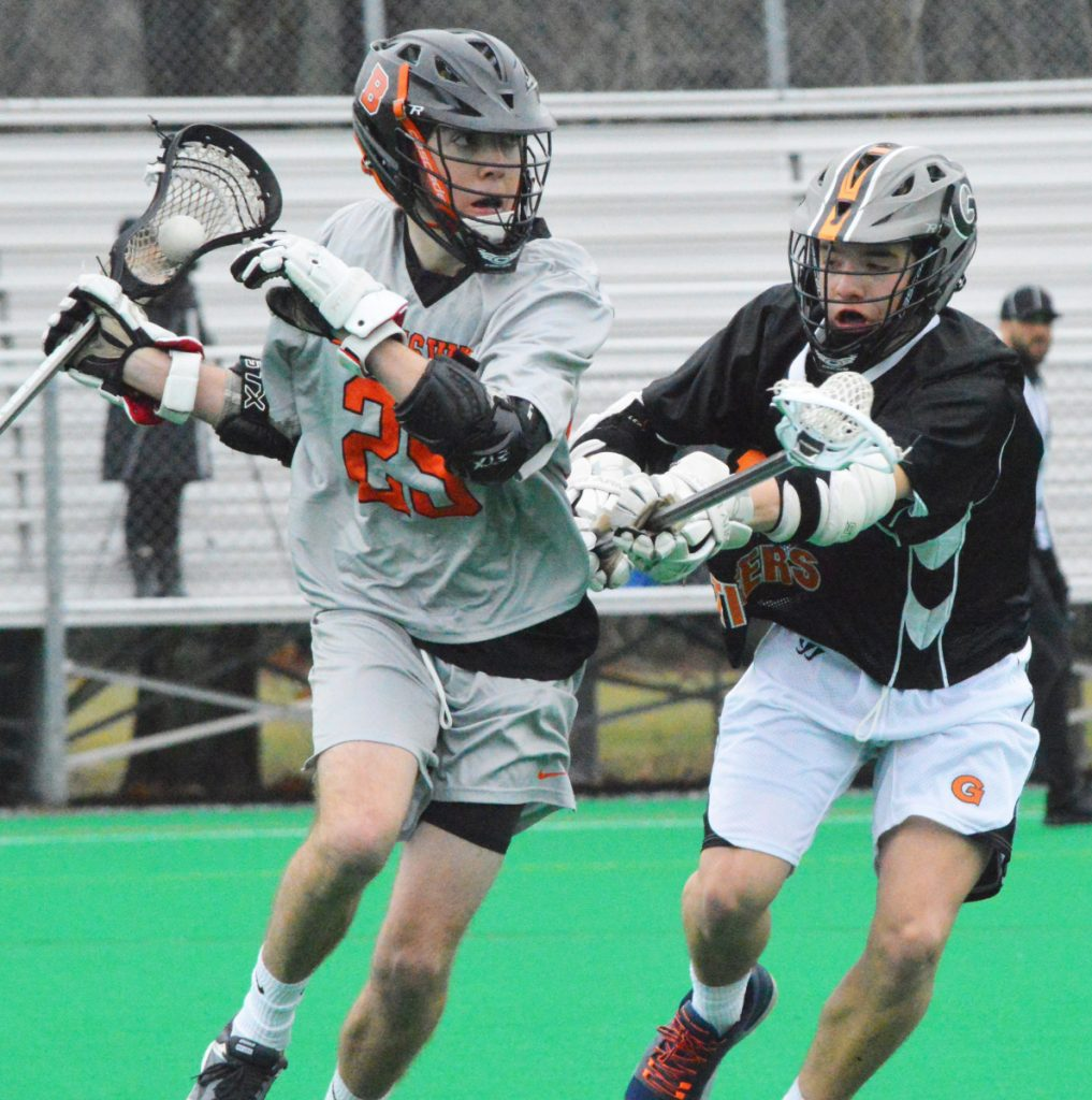 Brunswick's Jacob Belanger carries the ball with Shawn Michaud of Gardiner defending Tuesday at Bowdoin College. The Dragons improved to 2-0 with a 20-8 win.