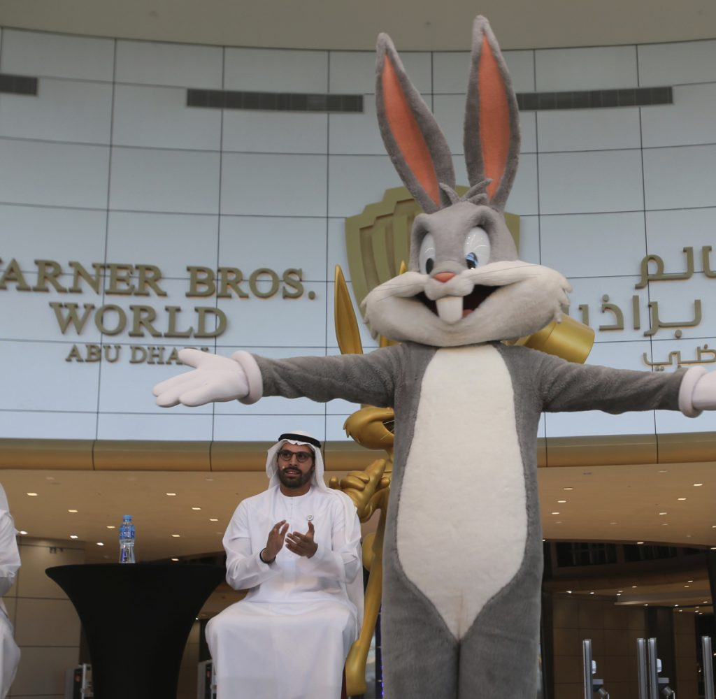 Mohamed Khalifa al-Mubarak, the chairman of both Miral and Abu Dhabi's Department of Culture and Tourism, claps for a Bugs Bunny character during a news conference in Abu Dhabi, United Arab Emirates, on Wednesday organized by the Warner Bros. World amusement park opening in July.