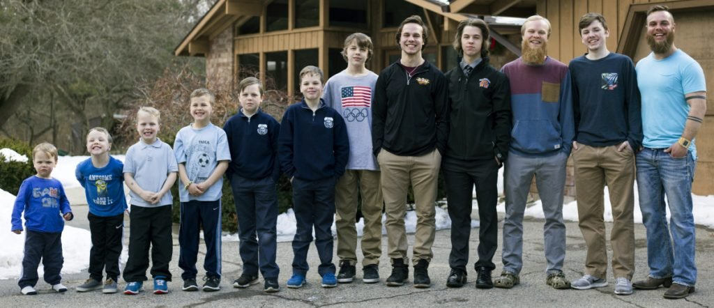 In this Feb. 2018 photo are, from left to right, brothers Francisco, 2, Tucker, 4, Luke, 6, Charlie, 8, Gabe, 11, Wesley, 9, Calvin, 13, Drew, 20, Tommy, 16, Zach, 22, Vinny, 15, and Ty Schwandt, 25, pose for a portrait at the Schwandt household in Grand Rapids, Mich. The only brother not pictured is Brandon, 18.