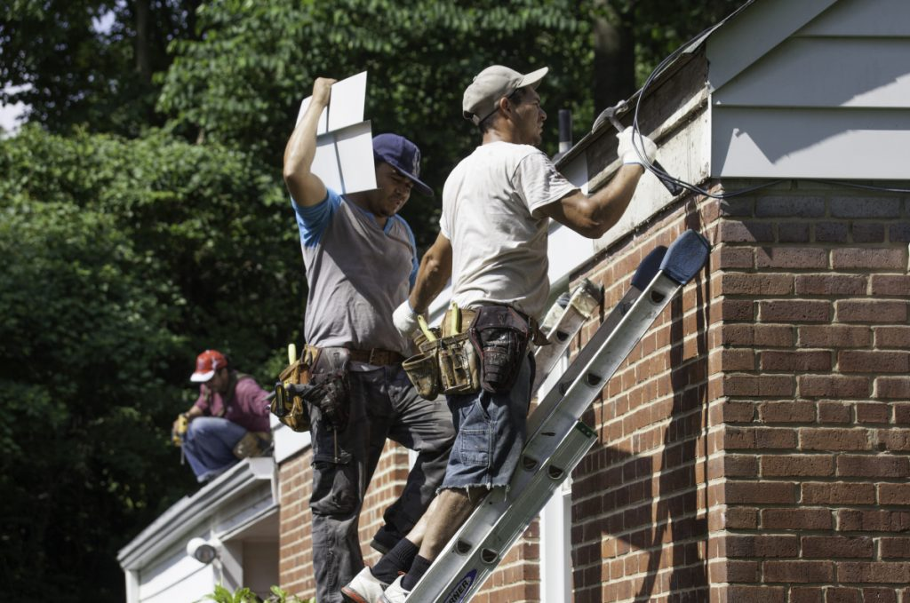 A work crew installs gutters and patches up a roof at a house in Fairfax County, Va. With an acute shortage of carpenters, electricians, plumbers and many other trade workers across the United States, many home owners are finding it difficult to maintain their properties.