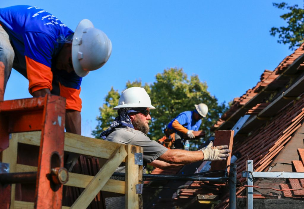 In this photo from 2015, construction workers lay tiles on the roof of a house in Boys Town, Neb. Repairing hail-damaged roofs in the village that sheltered at-risk youth since the 1930s is expensive because the campus is considered a national landmark with a look that has to be preserved. The repairs were financed with the help of the Nebraska Job Creation and Mainstreet Revitalization Act, a new state tax credit designed to revive historic buildings. (AP Photo/Nati Harnik)