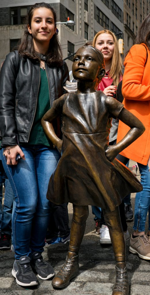 """Two girls pose for photos with the """"Fearless Girl"""" sculpture in lower Manhattan, New York."""