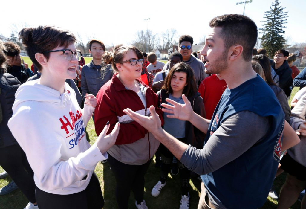 Elaine Flores, left, and Jared Baumann engage in a debate about gun control following the school walkout to protest gun violence Friday at West Lafayette High School in West Lafayette, Ind.