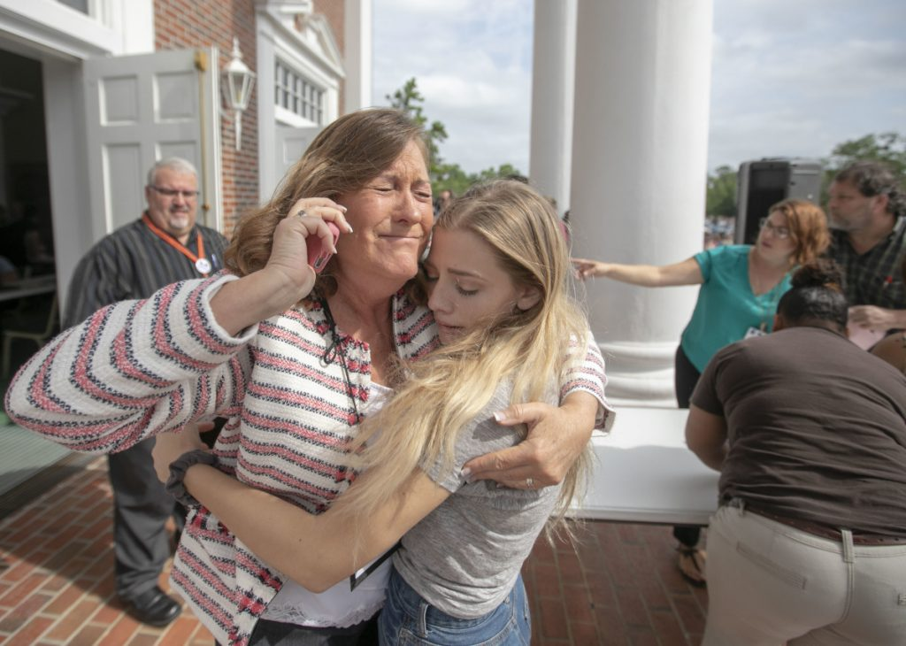 Judge Sarah Ritterhoff Williams embraces student Attie French, a family friend, after finding her in the crowd at First Baptist Church while looking for her own daughter following a shooting at Forest High School on Friday in Ocala, Fla.