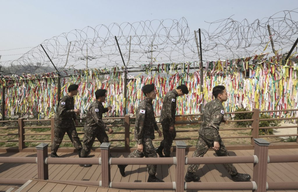 South Korean soldiers pass by a wire fence decorated with ribbons written with messages wishing for the reunification of the two Koreas at the Imjingak Pavilion in Paju, South Korea, near the border with North Korea, on Friday. North and South Korea installed the first-ever telephone hotline between their leaders Friday as they prepare for a rare summit next week aimed at resolving the nuclear standoff with Pyongyang.