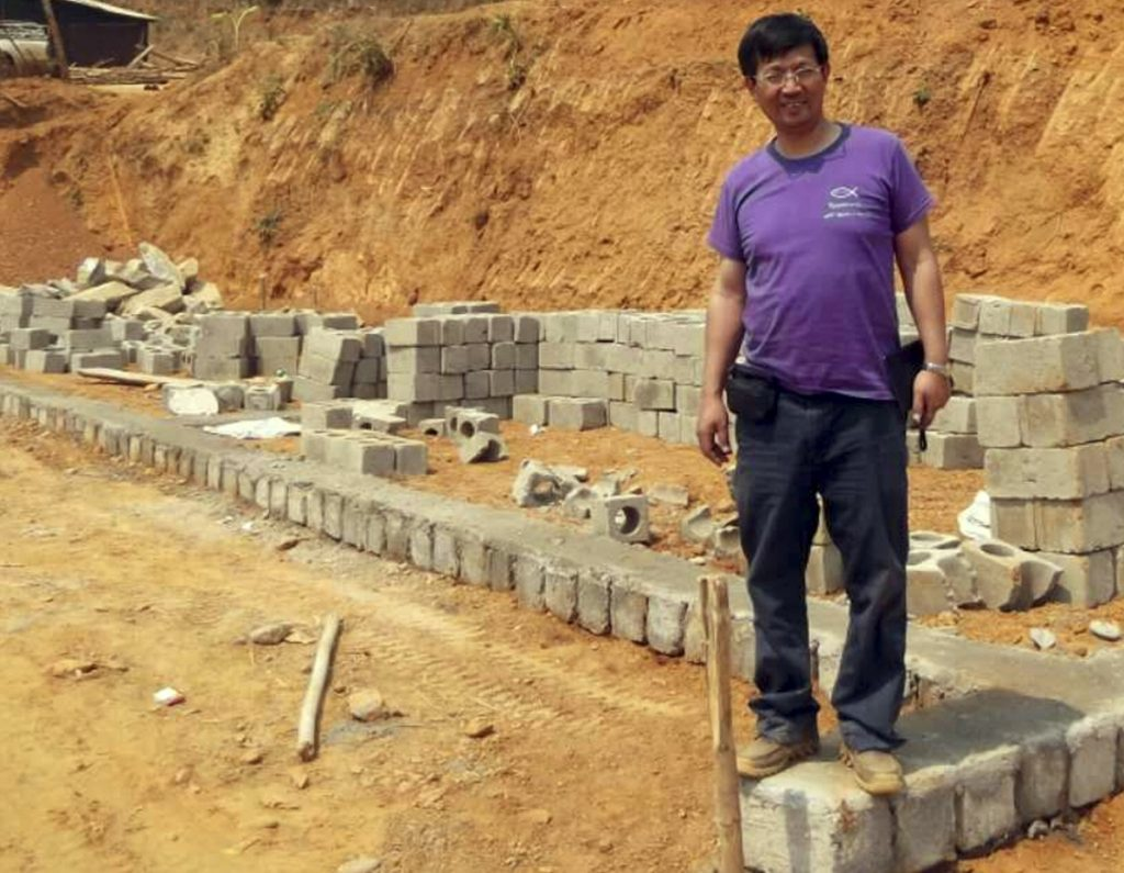 "The Rev. John Sanqiang Cao breaks a ground on a school in Myanmar in 2014. He was sentenced in China last month for ""organizing others to illegally cross the border."""