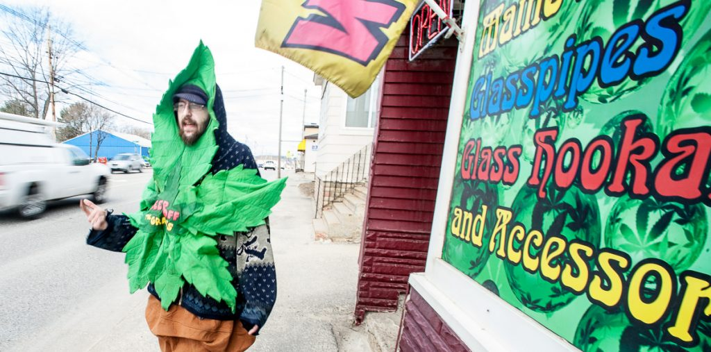 """Devin Urquart of Lewiston, whose alias is """"Blunt Man,"""" dances in front of Legal Peaces on Lisbon Street in Lewiston on Friday morning. """"It's 4/20, my favorite holiday and I'm just rocking out here to get some attention for the business,"""" he said."""