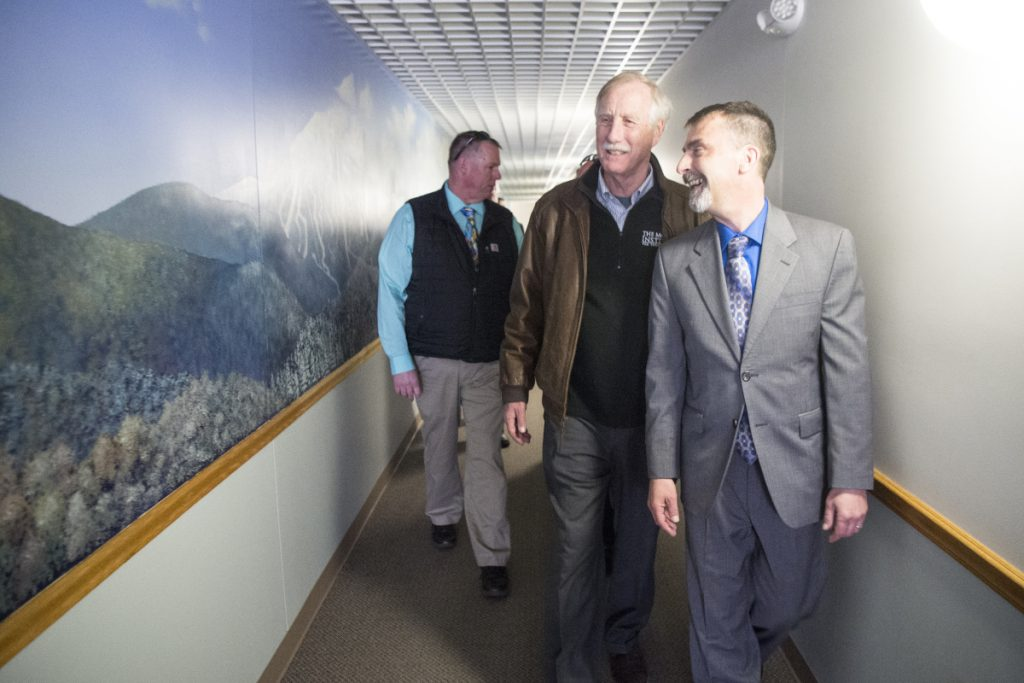David Cyr, right, vice president of Skowhegan Savings Bank, and U.S. Sen. Angus King, I-Maine, center, head to to the bank's security room where internet traffic is monitored. King talked to IT professionals there about the high number of cyberattacks the bank blocks daily.