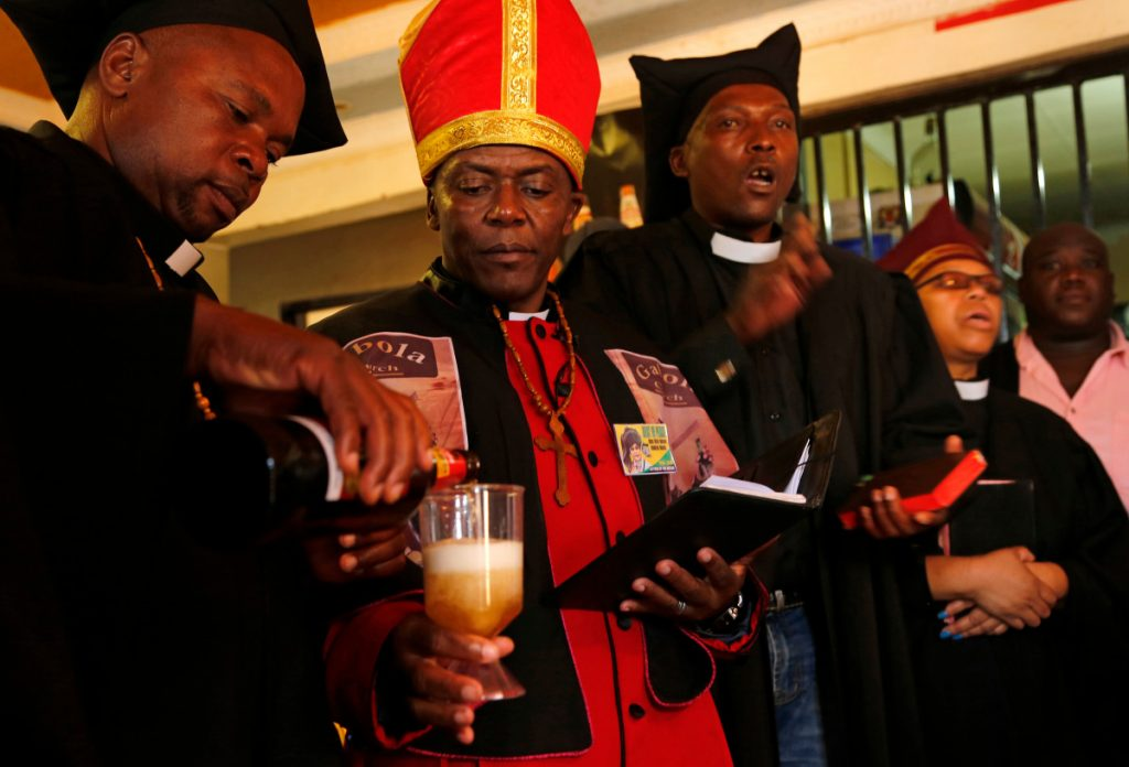 Self-proclaimed Pope Tsietsi Makiti, second left, prepares to baptize newcomers to this church.