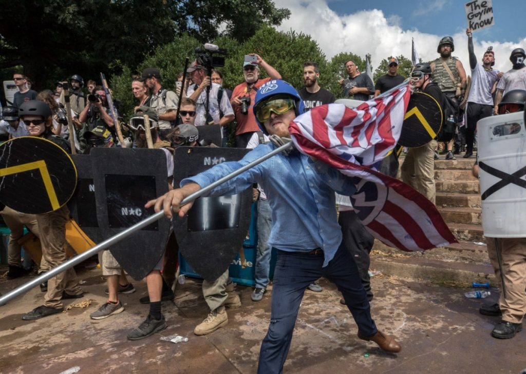 William Fears, center holding the flag, is pictured with other white supremacists at a Unite the Right rally in Charlottesville in August. The loose collection of white supremacist groups known as the alt-right movement has suffered significant setbacks since then.