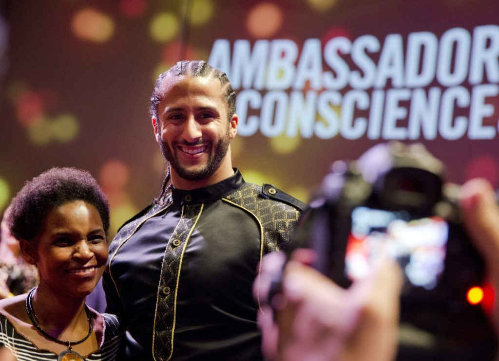Former NFL quarterback Colin Kaepernick poses with guests after wining the Amnesty International Ambassador of Conscience Award for 2018 in Amsterdam on Saturday.