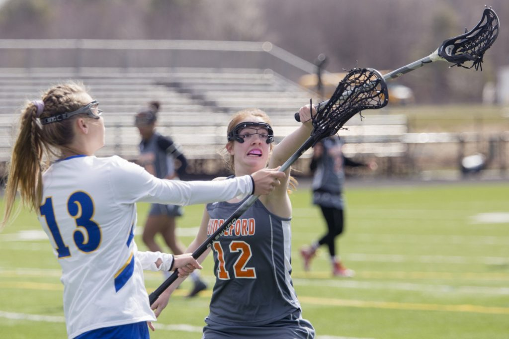 Biddeford's Jillian Lewis, right, tries to block a pass from Falmouth's Christina Oakes in the first half of Saturday's game. Falmouth opened an 11-2 lead and held on for an 11-8 victory in its first game of the season.