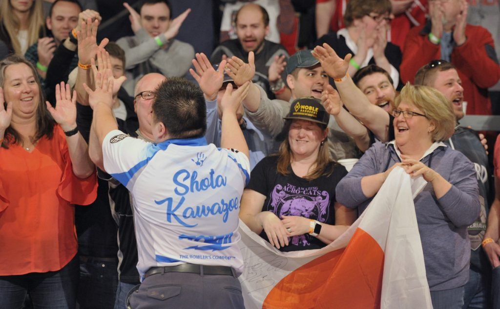 Shota Kawazoe of Japan high-fives fans after rolling a strike during the Elias Cup professional bowling event Saturday at Bayside Bowl in Portland. There were plenty of strikes and spares, but the packed crowd came for the fun, and found plenty of it.