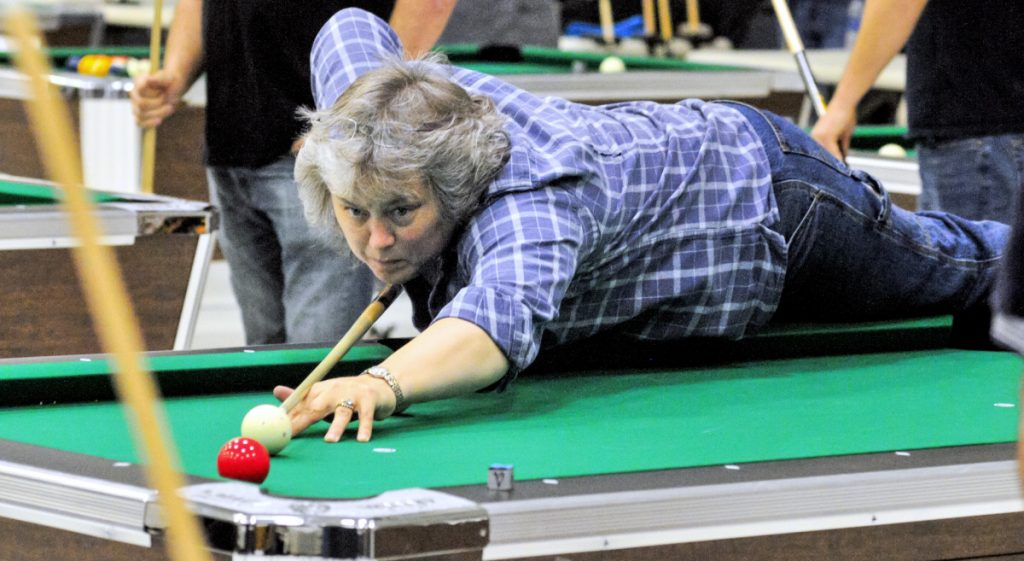 Manchester resident Chrystal Violette, a member of the Need a New Rack women's team, leans onto the table to make a shot during Sunday's event at the Augusta Armory.