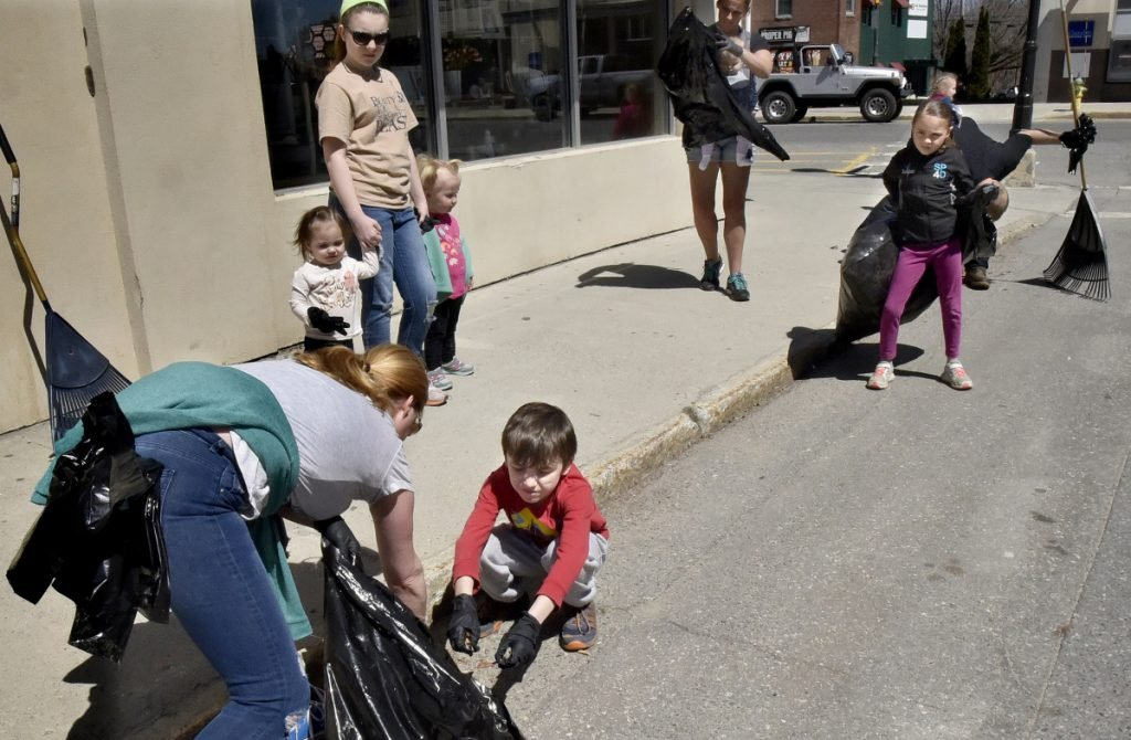 Molly Re holds a bag open for her son William to throw trash into as they and other family and friends helped pick up litter near the Concourse in Waterville as part of the Earth Day celebration on Sunday.