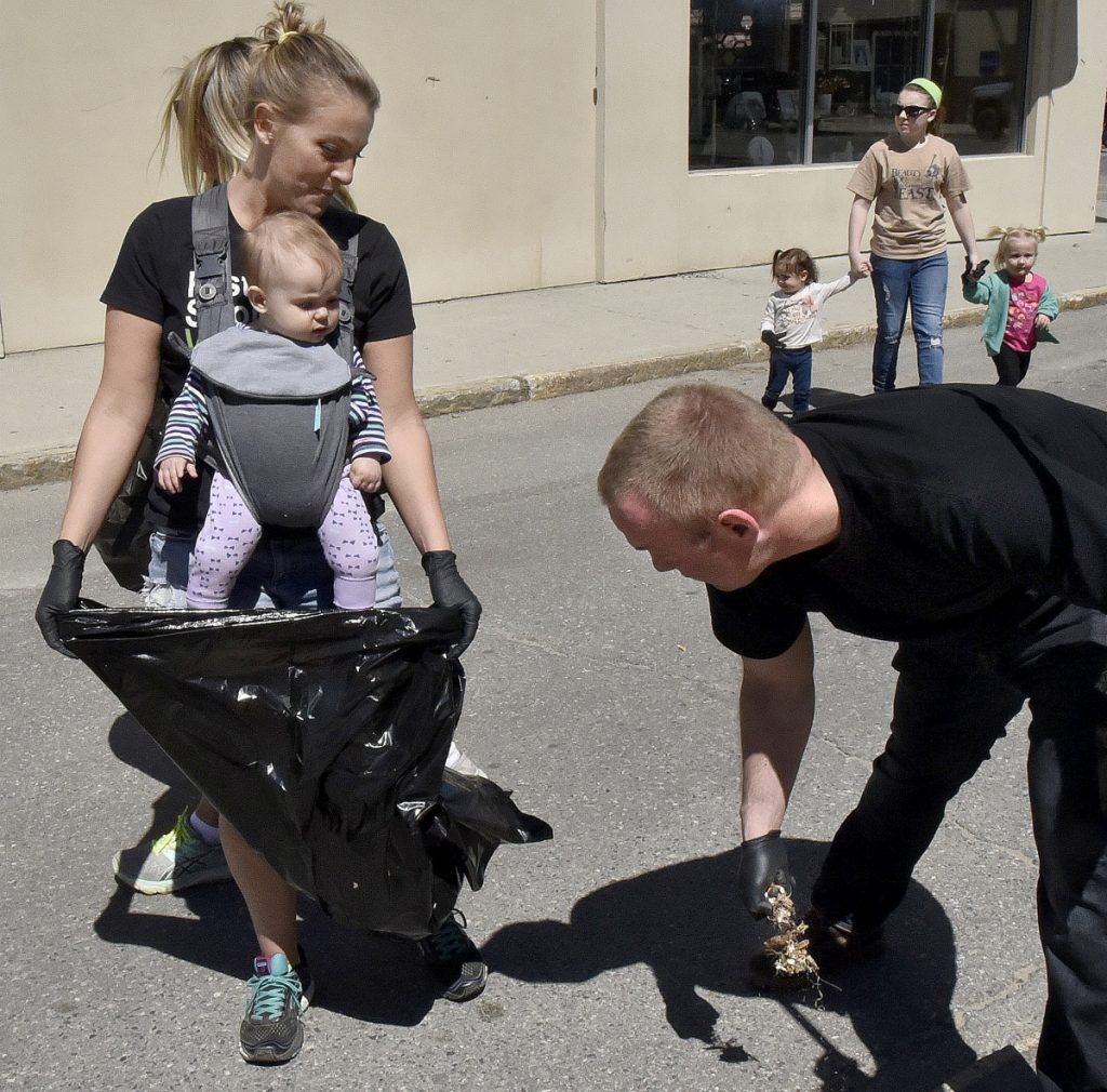 Molly Bofia with her daughter Isla Blue in a pack hold open a bag for Brian Clunie who along with others picked up litter near the Concourse in Waterville as part of the Earth Day celebration on Sunday.