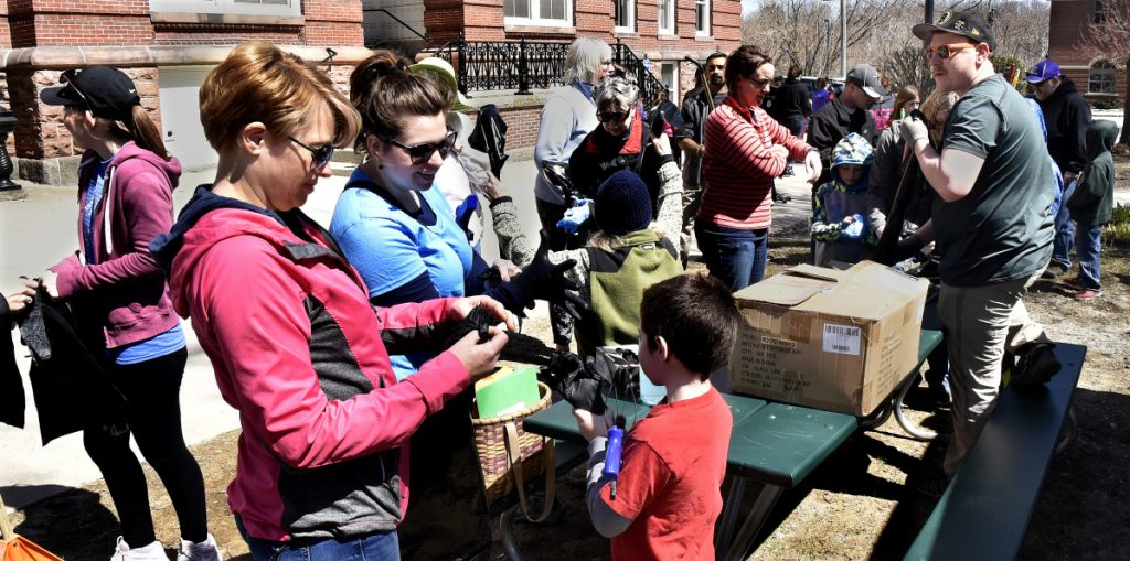 Todd Martin, right, hands out trash bags and gloves to volunteers who helped pick up litter near the Concourse in Waterville as part of the Earth Day celebration on Sunday.