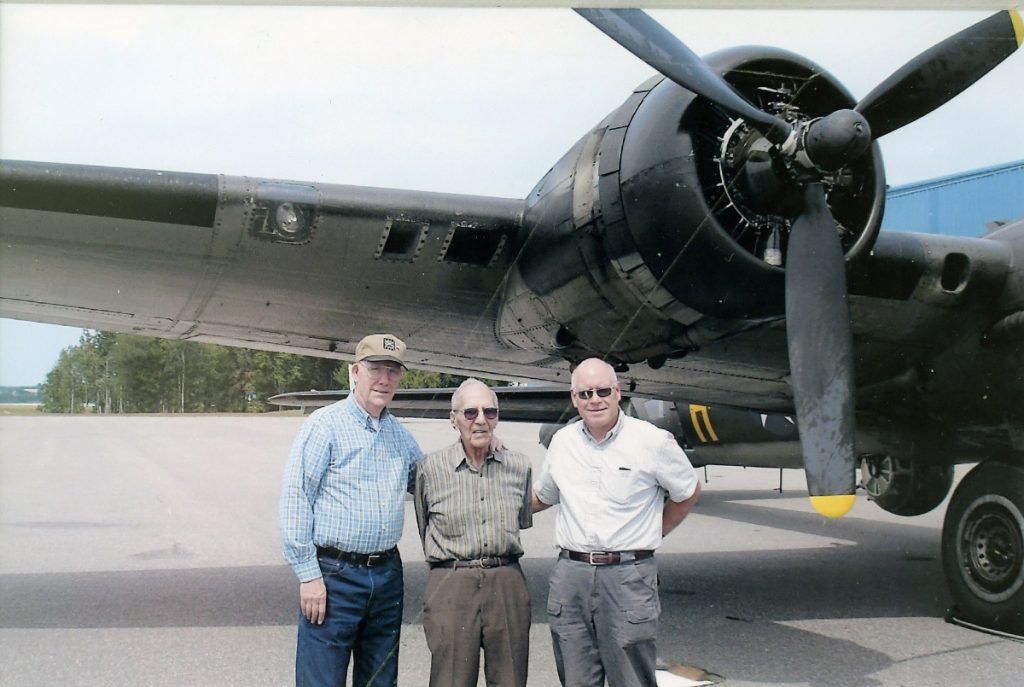 Al Kramer, center, with his neighbors from China village, Don Pauley, left, and Craig Poulin beneath the wing of a B-17 World War II bomber in New Hampshire in 2013. Kramer was shot down over France during WWII while piloting a B-17.