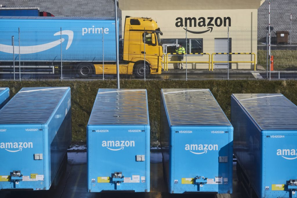 A truck pulling an Amazon Prime branded cargo container waits beside the entrance gate at an Amazon.com Inc. fulfillment center.