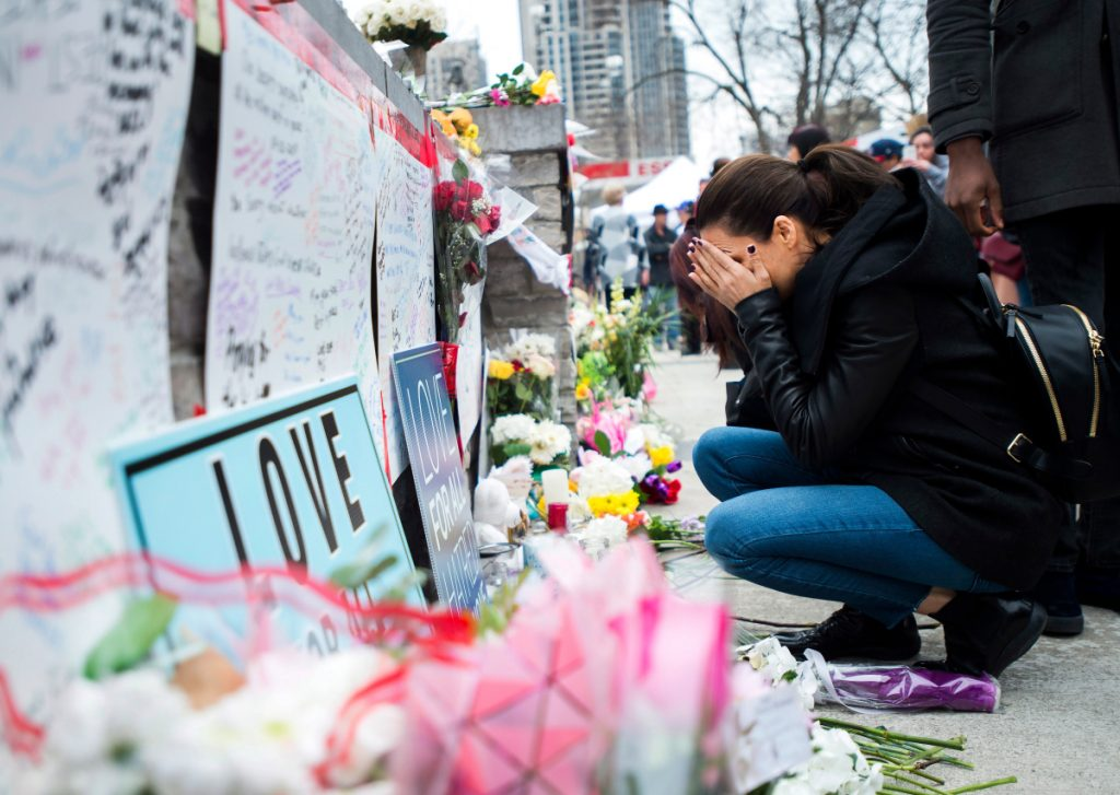 A women fights back tears at a memorial along Yonge Street on Tuesday in Toronto, the day after a driver drove a van down sidewalks, striking and killing numerous pedestrians in his path.