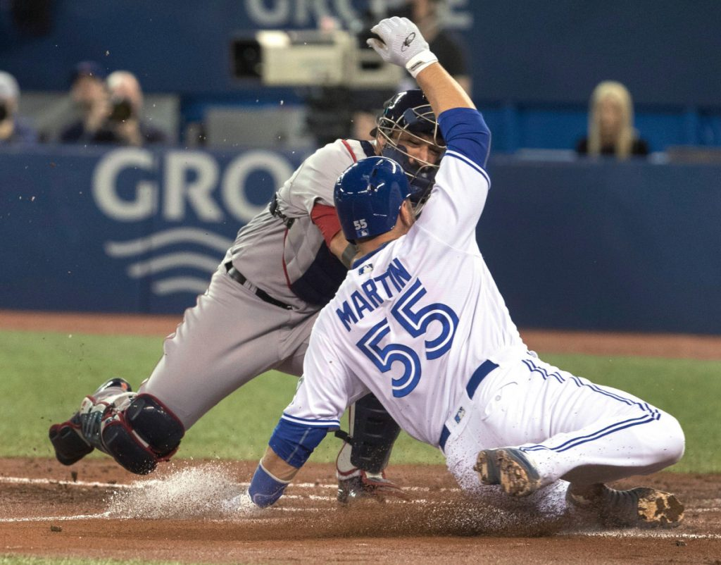 Red Sox catcher Sandy Leon tags out Toronto's Russell Martin at the plate in the second inning Tuesday at Toronto. The Blue Jays beat the Sox 4-3 in 10 innings.