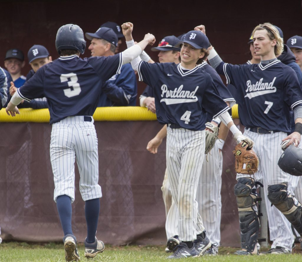 Portland players congratulate junior Ben Stasium, 3, after he scores a run during Portland's 8-1 win over Thornton Academy on Saturday in Saco.