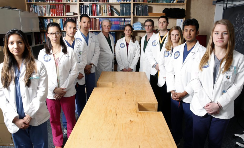 University of New England students and staff surround a bare cadaver table. UNE has the state's only licensed medical school with a whole-body donation program.