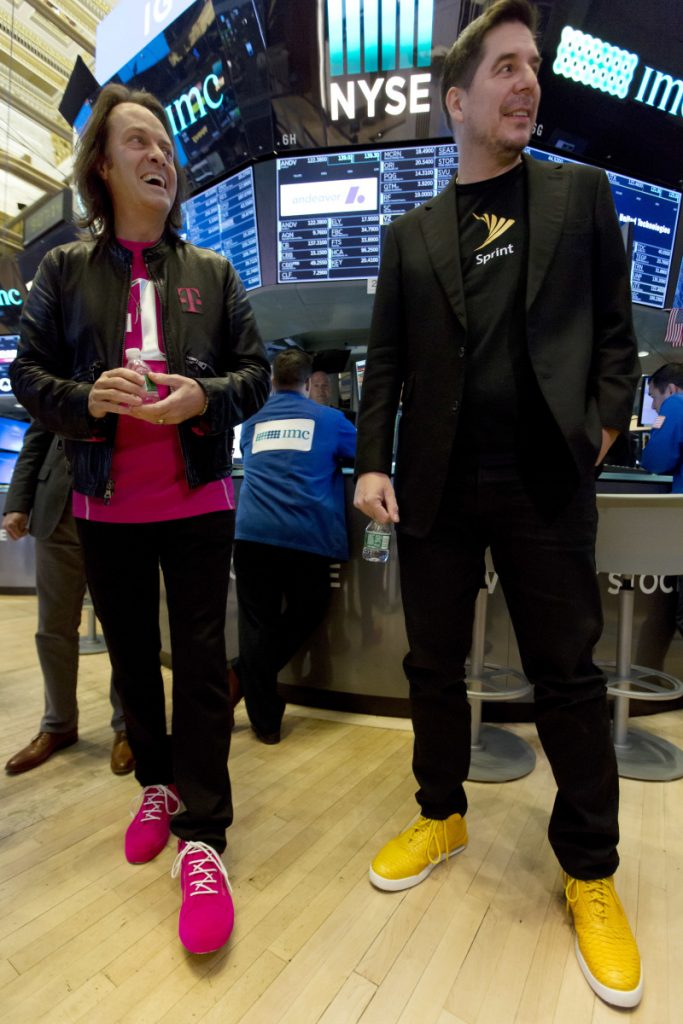T-Mobile CEO John Legere, left, and Sprint CEO Marcelo Claure wear their signature colored shoes Monday on the first day the New York Stock Exchange was open after T-Mobile and Sprint said they would merge into a company with 127 million customers.