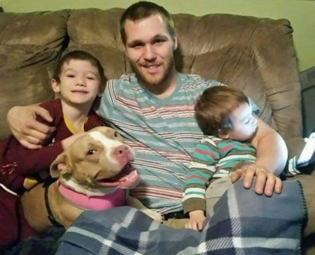 Mitchell MacArthur Jr., sits flanked by his sons Logan (left) and Owen, and Sabrina, the rescue dog the family adopted that alerted MacArthur to a fire in his Somerset Ave. home in Fairfield Sunday night.