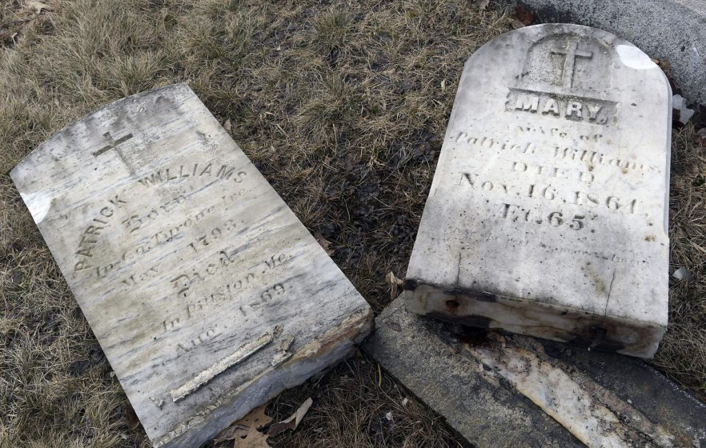 The damaged headstones of Irish immigrants are seen last month at St. Denis Cemetery in Whitefield after a car crashed into the cemetery.