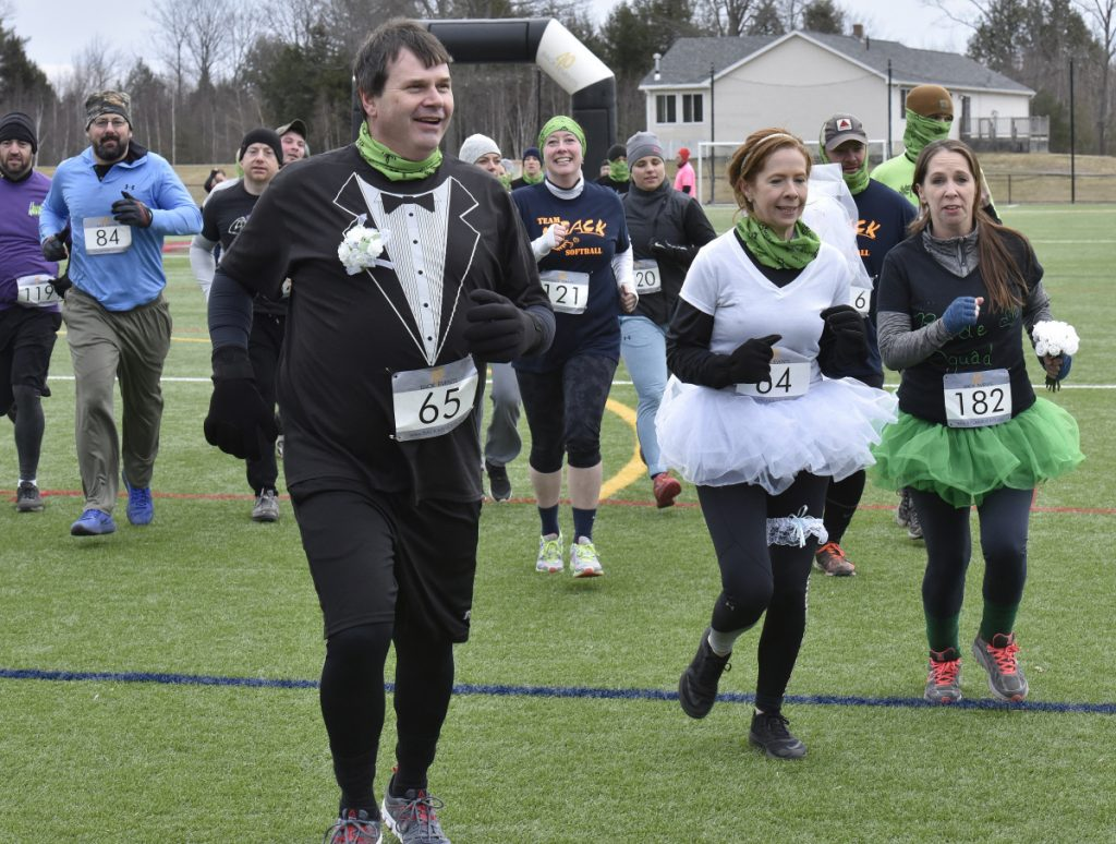 Bill Jackson and Jennifer Denis, both of Randolph, wore wedding outfits as they take off running in the Thomas College Dirty Dog Mud Run.