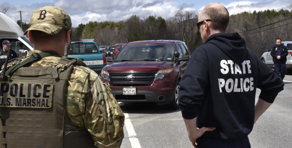 Police from numerous local, state and federal agencies watch as murder suspect John Williams, in cruiser, is taken from the scene in Fairfield after being apprehended on Saturday following a four-day manhunt for the killing of Somerset Cpl. Eugene Cole on April 25.