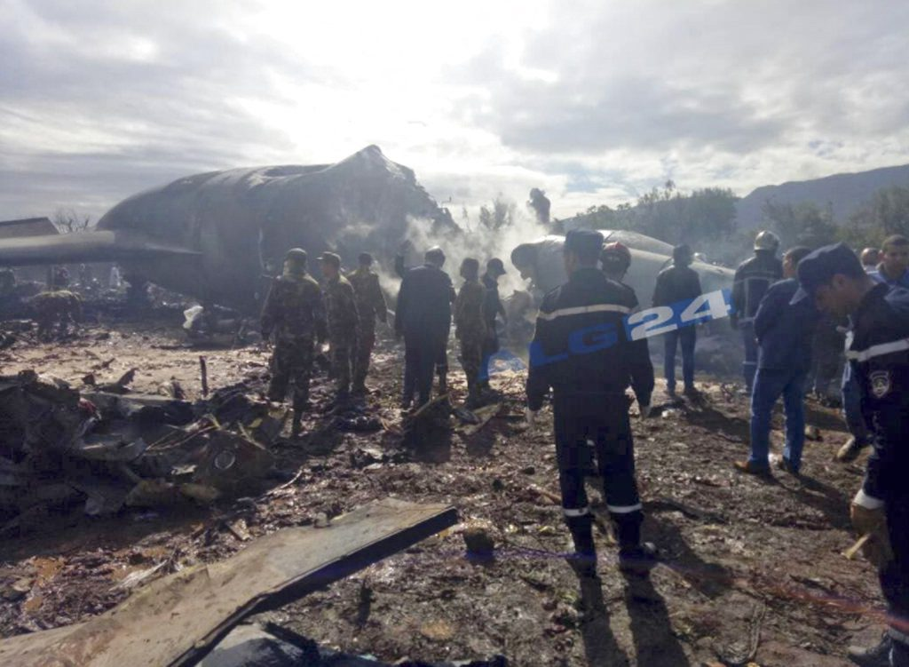 This image posted by Algerian news agency ALG24 shows firefighters and soldiers at the scene of the fatal plane crash near Boufarik military base near the Algerian capital, Algiers.