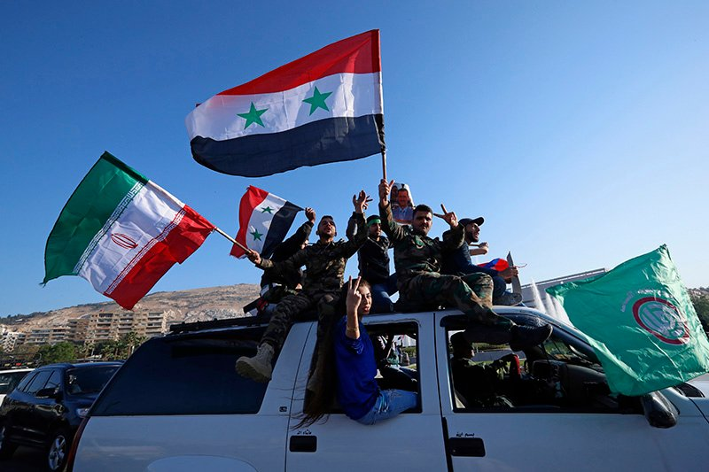 Syrian government supporters wave Syrian, Iranian and Russian flags as they chant slogans against U.S. President Trump during demonstrations following a wave of U.S., British and French military strikes .