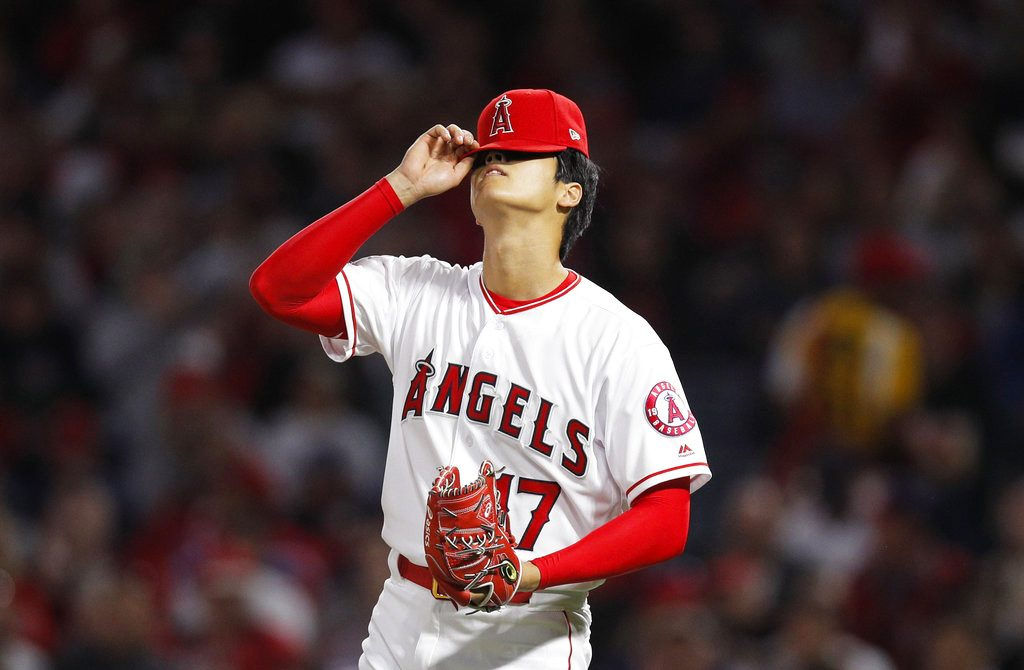 Shohei Ohtani adjusts his hat during the second inning in Anaheim. His impressive opening month has drawn unprecedented early season attention and Tuesday night's home crowd was the Angels' second-biggest since the year 2000.