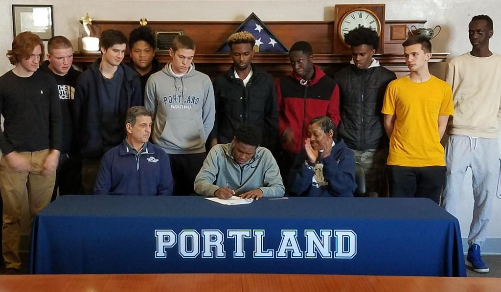 Portland senior standout Terion Moss, joined by his mother, Valerie, Bulldogs coach Joe Russo and several teammates, signs his National Letter of Intent Wednesday morning.
