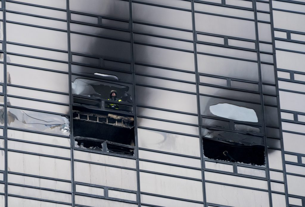 A firefighter looks out from the window of a fire-damaged apartment in Trump Tower in New York on Saturday. The Fire Department said the blaze broke out on the 50th floor shortly before 6 p.m.