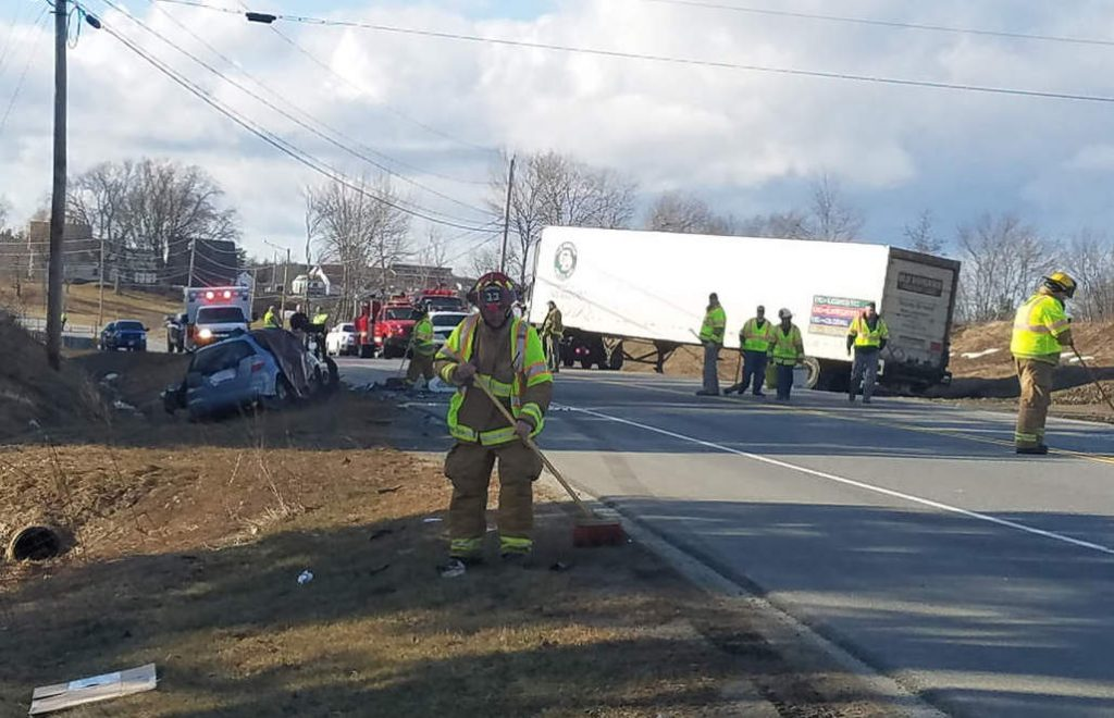 Firefighters clean up at the scene of Monday's fatal crash on Route 1 in Warren.
