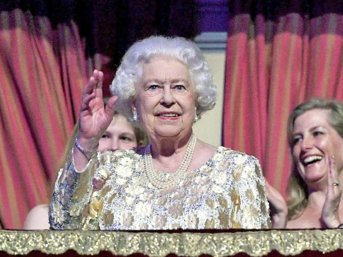 Queen Elizabeth II, surrounded by members of the royal family, waves to the crowd at the Royal Albert Hall in London on Saturday.