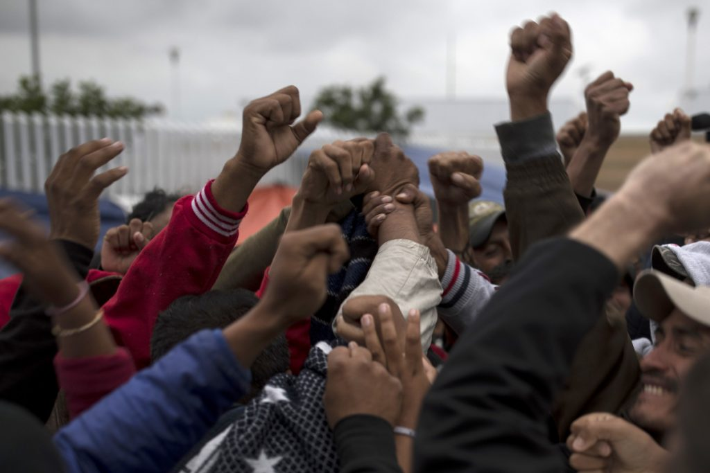 Associated Press/Hans-Maximo Musielik Migrants cheer and celebrate after hearing the news U.S. border inspectors allowed some of the Central American asylum-seekers to enter the country for processing, in Tijuana, Mexico, on Monday, ending a brief impasse over lack of space.