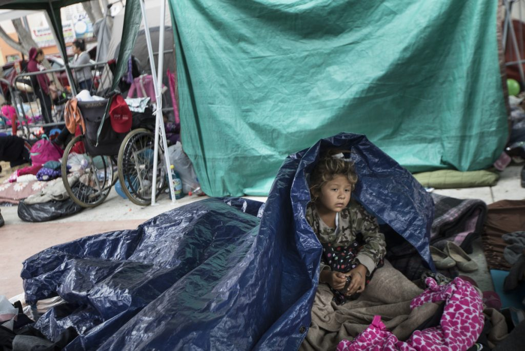 A girl who traveled with the caravan of Central American migrants awakens where the group set up camp to wait for access to request asylum in the U.S., outside the El Chaparral port of entry building at the US-Mexico border in Tijuana, Mexico, on Tuesday.
