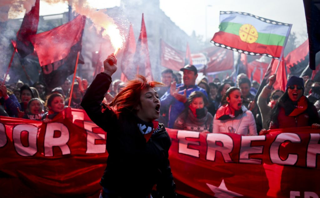 Above, a woman holds a flare as a crowd demands that the government address labor issues during the annual May Day march Tuesday in Santiago, Chile. Below, people march in the center of Barcelona, Spain.