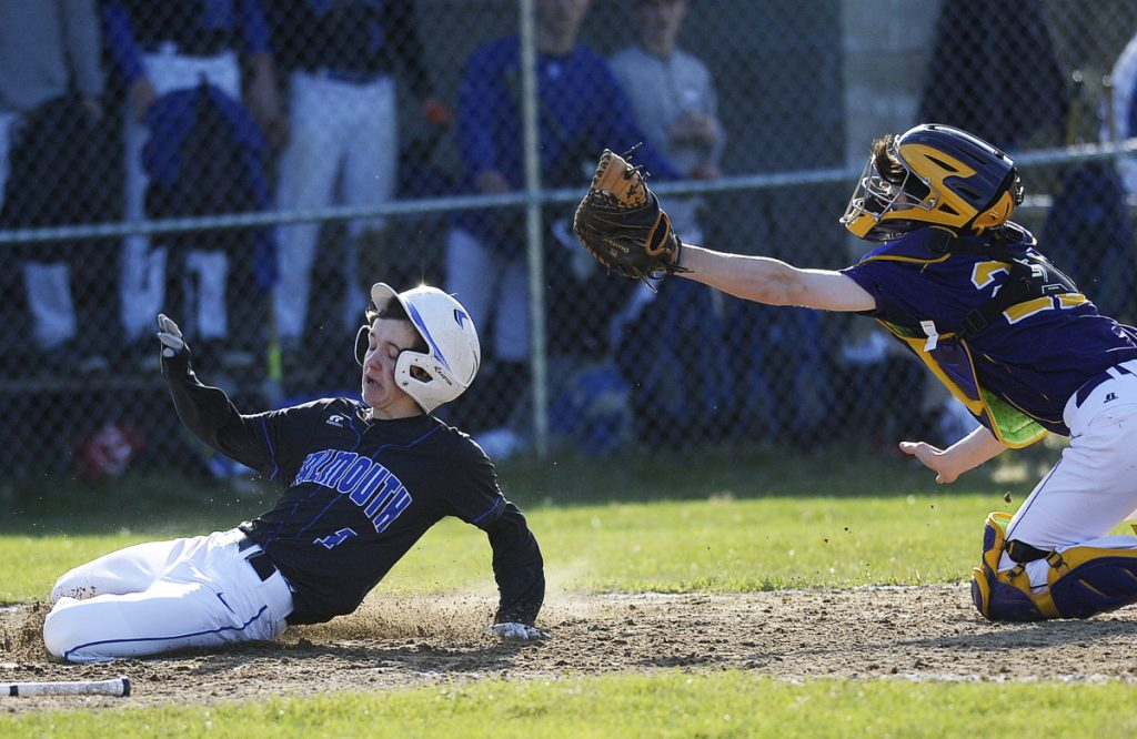Falmouth's Connor Coffin slides under the tag of Cheverus catcher Andrew Young in Tuesday's game at Falmouth. The Yachtsmen went ahead for good in the third inning to win 3-1.